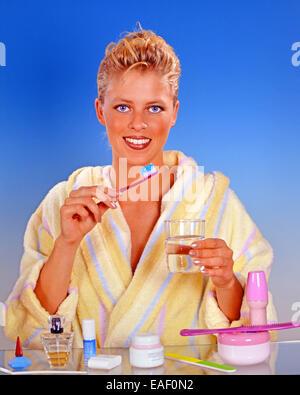 Blonde Frau, die ihre Zähne putzen - Stockfoto