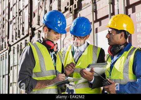 Unternehmer und Arbeiter in der Nähe von Containern im Gespräch - Stockfoto