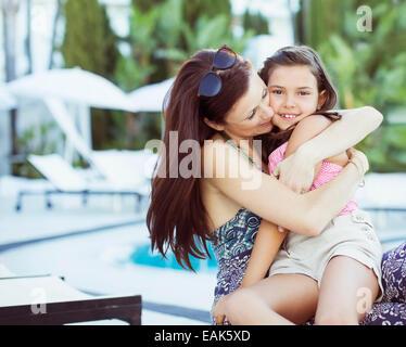 Mutter umarmte ihre Tochter am Pool - Stockfoto