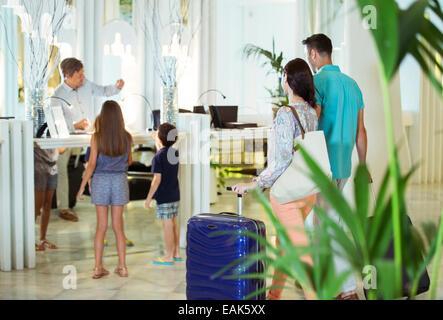 Familie mit zwei Kindern an Rezeption in der Lobby des Hotels - Stockfoto