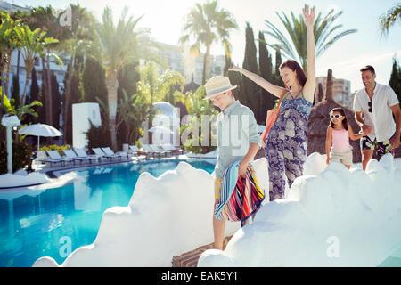 Glückliche Familie mit zwei Kindern zu Fuß mit Swimmingpool - Stockfoto