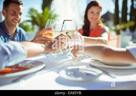 Freunde, die Erhöhung der Toast am Tisch im freien - Stockfoto
