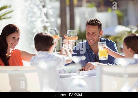 Familie mit zwei Kindern, die Erhöhung der Toast am Tisch im freien - Stockfoto