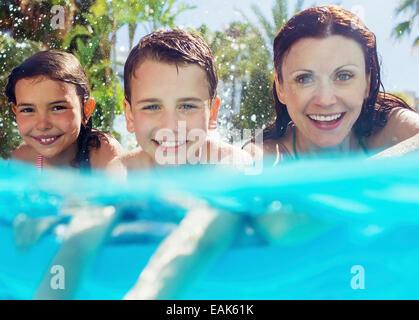 Porträt der Mutter mit ihren zwei Kindern im Schwimmbad - Stockfoto