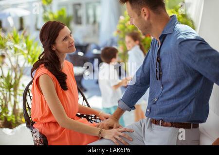 Mann und Frau sitzen im Freien, von Angesicht zu Angesicht Kinder im Hintergrund - Stockfoto