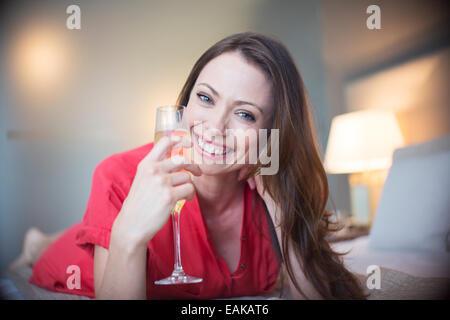 Porträt der lächelnde Frau auf Bett liegend mit Sektglas - Stockfoto