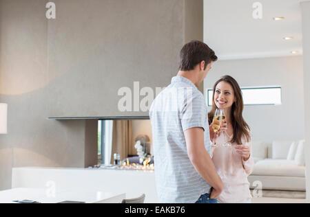 Lächelnde paar raising Toast mit Sektgläser im Wohnzimmer - Stockfoto