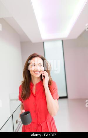 Lächelnde Frau mit roten Kleid telefonieren im Haus Flur - Stockfoto