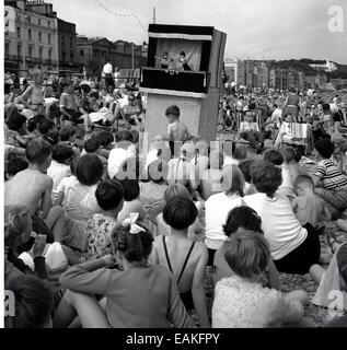 1950er Jahre, historisch, ein traditionelles Punch & Judy Puppentheater unterhält die Urlauber an einem überfüllten - Stockfoto