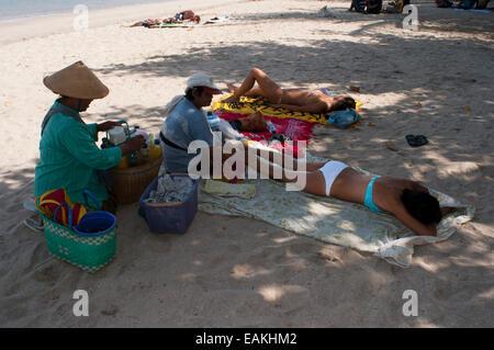 Indonesien, Bali, Kuta, Strand, Frau Essen Massage.  Sonnenbad am Strand von Kuta. Surfunterricht. Bali. Kuta ist - Stockfoto