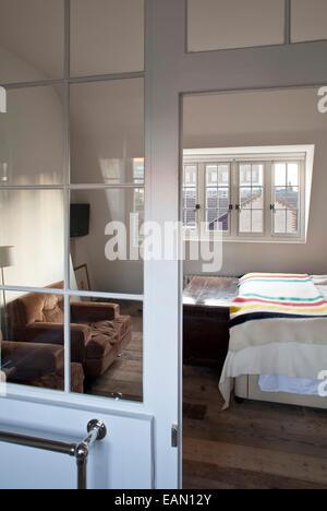 Doppelbett im Dachgeschoss Zimmer mit schrägen Decke im georgianischen Stadthaus, Whitechapel, London - Stockfoto