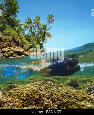 Über-unter in das Karibische Meer mit Schnorchler unter Wasser in einem flachen Korallenriff und über Oberfläche, - Stockfoto