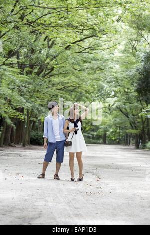 Ein paar, Mann und Frau in einem Kyoto-Park in eine Allee von Bäumen. - Stockfoto
