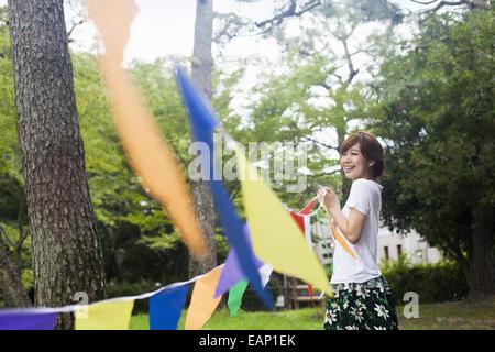 Eine Frau in einem Kyoto-Park eine bunte Reihe von Fahnen hochhalten. - Stockfoto