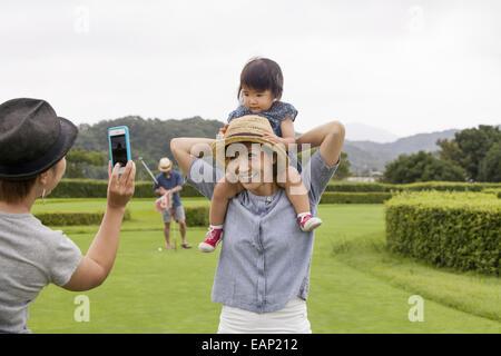 Familie auf einem Golfplatz. Ein Kind auf eine Frau Schultern. - Stockfoto