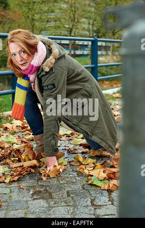 Frau, die ein Ausrutschen auf nassen Herbstlaub - Stockfoto