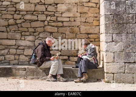 Taking a Break from Touring. Zwei mittleren Alters Touristen machen Sie eine Pause auf Steinbank unter Asyl Wand - Stockfoto