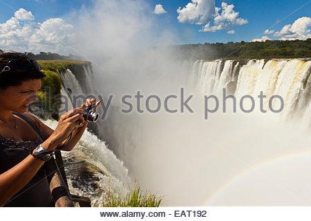 Eine Frau nimmt ein Foto von Iguazu Wasserfälle von einem Aussichtspunkt. - Stockfoto