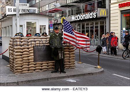 Ein Schauspieler verkleidet als Soldat der United States Army eine amerikanische Flagge am Checkpoint Charlie, der - Stockfoto