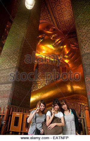 Touristen stehen vor der riesigen Buddha im Wat Pho Tempel. - Stockfoto