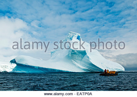 Touristen auf einem Schlauchboot erkunden einen riesigen Eisberg. - Stockfoto
