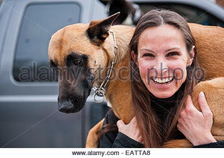 Eine Frau trägt ihr Hund in Bella Coola, Britisch-Kolumbien. - Stockfoto
