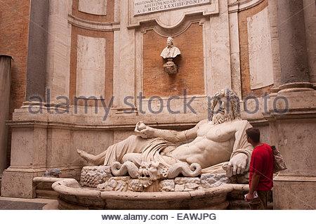 Ein Tourist bewundert die Statue des Oceanus Marforio. - Stockfoto
