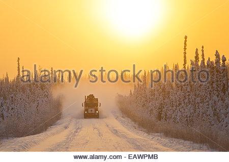 Ein semi-LKW bei Sonnenuntergang Reisen durch verschneite Wälder auf dem Dempster Highway. - Stockfoto