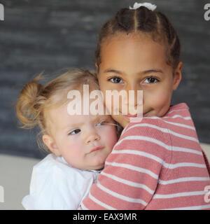 Mädchen umarmt Babymädchen, Porträt - Stockfoto