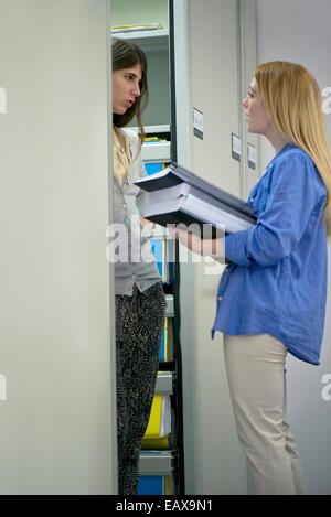 Frauen diskutieren Dateien im Büro - Stockfoto