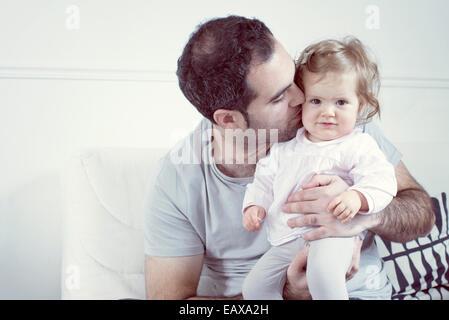 Vater hält Babymädchen auf Schoß, ihre Wange küssen - Stockfoto