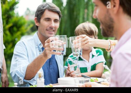 Familie klirrende Gläser im freien - Stockfoto