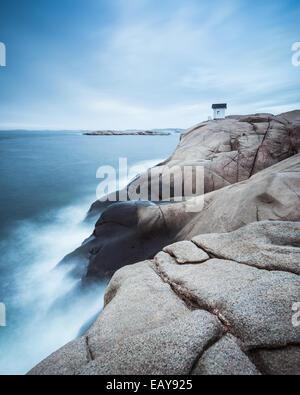 Kabine auf Klippe in der Nähe von Meer mit dramatischer Himmel - Stockfoto
