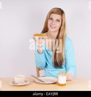 junge Frau beim Frühstück mit Toast, Marmelade und Kaffee - Stockfoto