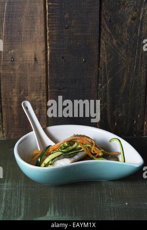 Seehecht in Brühe mit Karotten und Zucchini auf dunklem Hintergrund - Stockfoto