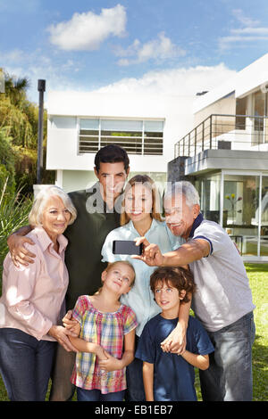 Glückliche Familie, die eine Selfie mit Handy im Garten vor einem Haus - Stockfoto