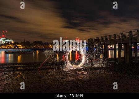 Lightpainting, Spinnen beleuchtet Stahlwolle auf einem Themse-Strand in der Nacht - Stockfoto