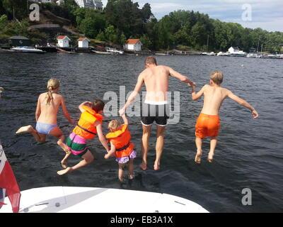 Mann und vier Kinder springen von einem Boot ins Meer, Norwegen - Stockfoto