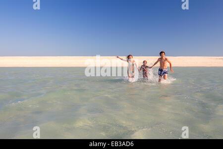 Drei Kinder laufen ins Meer, Western Australia, Australien - Stockfoto