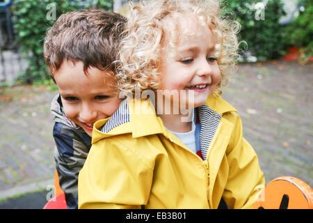 Lächelnden jungen und Mädchen sitzen auf Frühling reiten auf Spielplatz Stockfoto