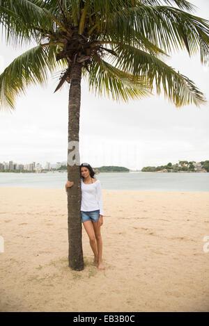 Lächelnde Frau umarmt Palme am tropischen Strand - Stockfoto