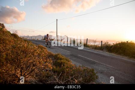 Frankreich, Korsika, Rennrad über Meer bei Sonnenuntergang - Stockfoto