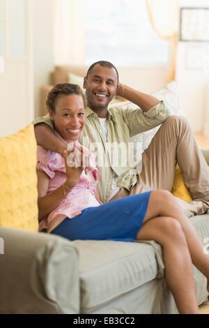 Paar lächelnd auf dem Sofa im Wohnzimmer - Stockfoto