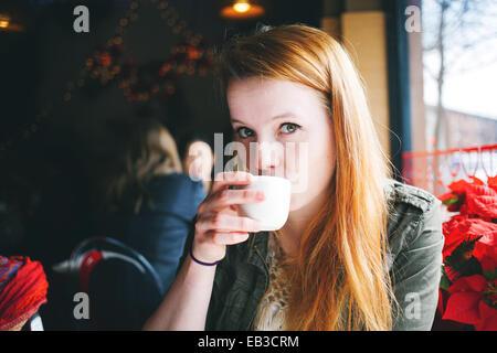 USA, Illinois, Chicago, Porträt der jungen Frau, die aus weißen Tasse im Restaurant schlürfen - Stockfoto