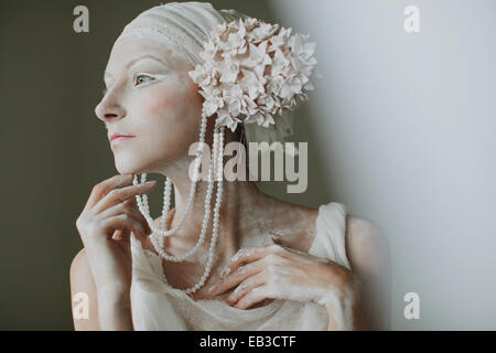 Portrait von junge Frau trägt Make up, Schminke, Perlen und Ohr Dekorationen ähneln Blütenstand