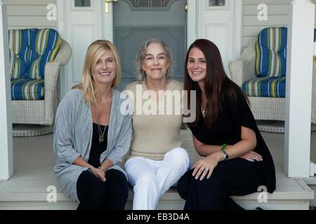 Kaukasische Mutter und Töchter, die lächelnd auf Veranda - Stockfoto