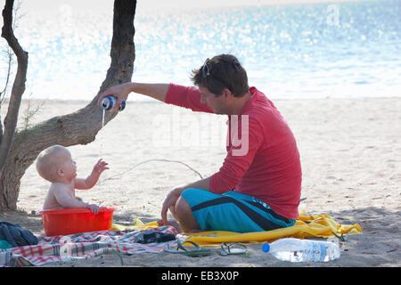 Man gießt Wasser auf Baden baby - Stockfoto