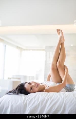 Junge Frau auf Bett liegend - Stockfoto