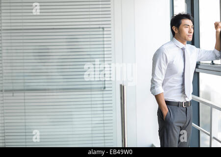 Junger Geschäftsmann Blick durch Fenster - Stockfoto