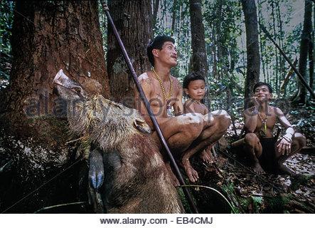 Zwei Männer der Penan und ein kleiner Junge ruhen, während ein totes Wildschwein, Sus Barbatus, zurück in ihr Lager - Stockfoto